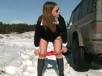Girl pissing on snow near the car