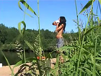Brunette teen peeing near the lake