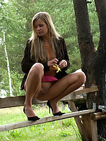 Blondie pisses onto the bench she's sitting on