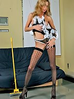 Blonde maid Lady B in stockings posing with yellow broom and taking panties off