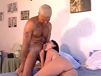 Slim brunette sucking grizzled hunk