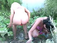Two precious bikini babes peeing into the lake